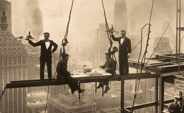 Construction workers sitting on beams suspended high above New York City while eating a gourmet meal.
