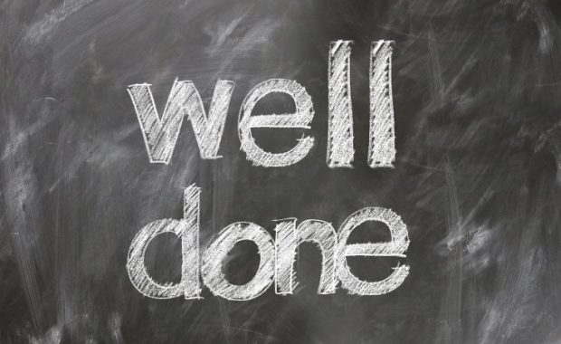 "A chalkboard with the words ""Well Done"" written on it."